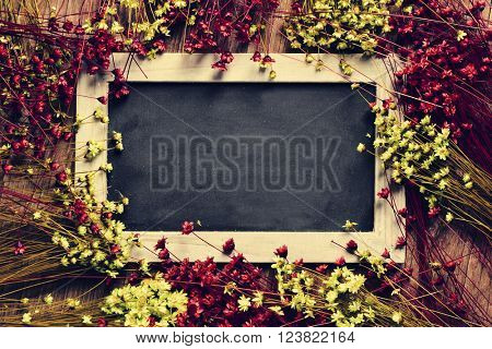 a blank wooden-framed chalkboard surrounded by red and yellow small flowers