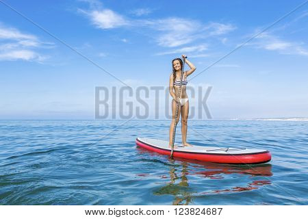 A beautiful woman practicing paddle on a beautiful sunny day
