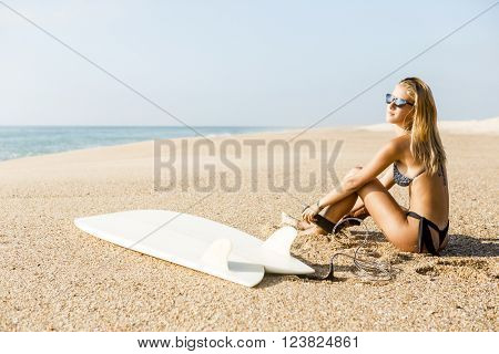 Beautiful surfer girl getting ready to surf and putting the leash