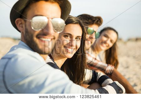 Friends sitting at the beach and having fun