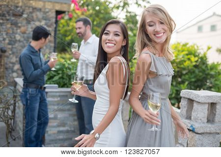 Two attractive ladies dancing at cocktail party