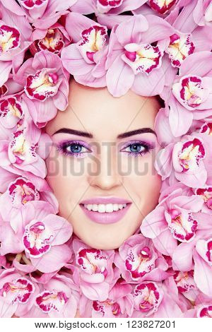 Vintage style portrait of young beautiful smiling woman with stylish make-up and pink orchids around her face