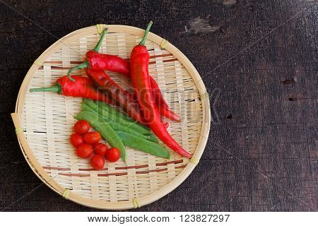 Chili, sweet peas and cherry tomato on rattan tray on old wooden table. Selected focus.