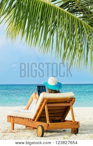 Woman relaxing with tablet on deckchair