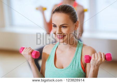 fitness, sport, training and lifestyle concept - happy smiling young woman with dumbbells exercising in gym