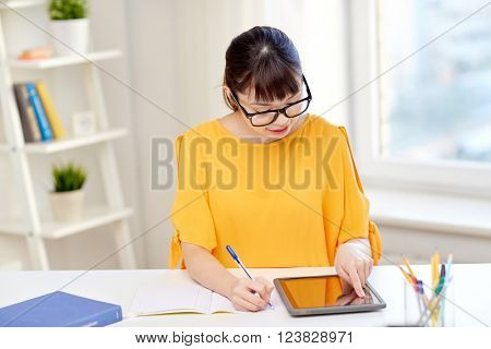 people, education, high school and learning concept - happy asian young woman student in glasses with tablet pc computer, book and notepad writing at home