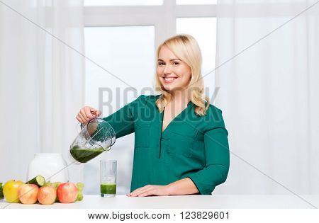healthy eating, cooking, vegetarian food, diet and people concept - smiling young woman with blender shaker jug pouring green vegetable smoothie or juice into glass at home kitchen