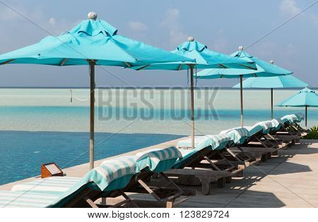 travel, tourism, vacation and summer holidays concept - parasol and sunbeds over sea and sky on maldives beach