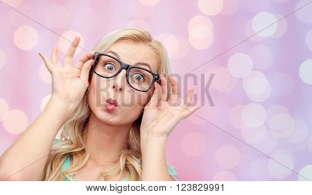 vision, education and people concept - happy young woman or teenage girl glasses making funny fish face over pink holidays lights background