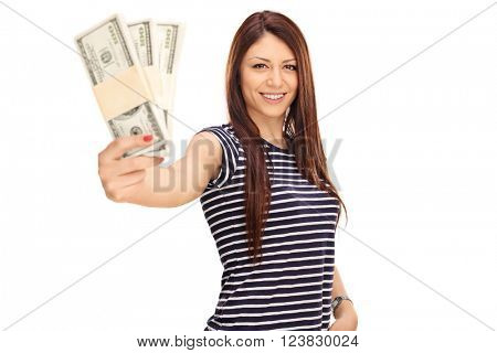 Cheerful young woman holding a few stacks of money and looking at the camera isolated on white background
