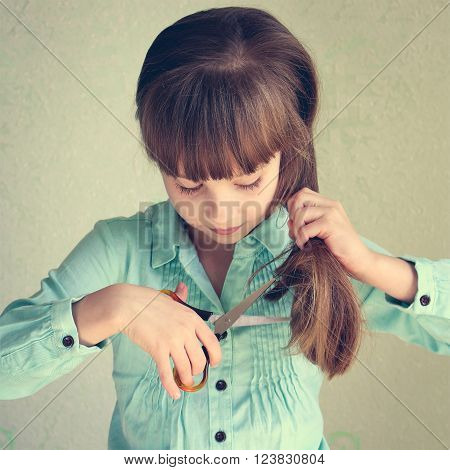 Little girl cut her hair. Toned image.