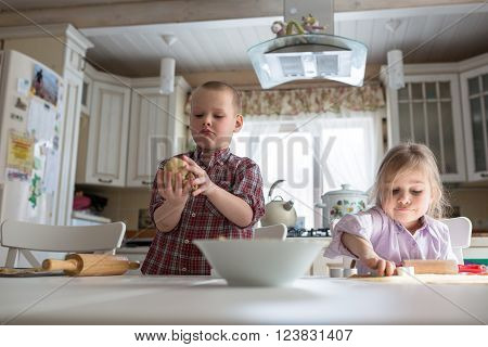 brother and sister silings children preparing cookies in the kitchen large family. casual lifestyle photo series in real life interior