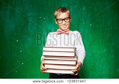 Clever schoolboy with stack of books