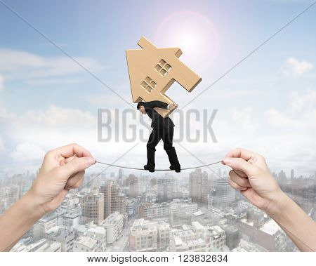 Man carrying wooden house and balancing on tightrope with two hands pulling on sunny sky cityscape background.