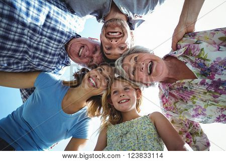 Laughing family forming huddle in back yard against sky