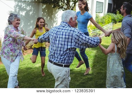 Multi-generation family playing ring around rosie in back yard