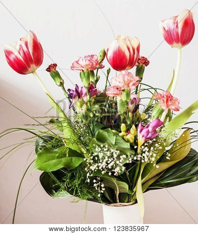 Beautiful bouquet of tulips carnations and freesia. Holiday symbol. Seasonal flowers.
