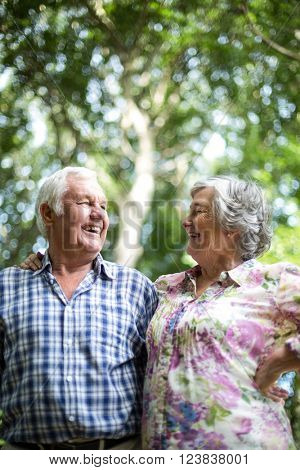 Happy senior couple laughing while looking at each other against trees in back yard