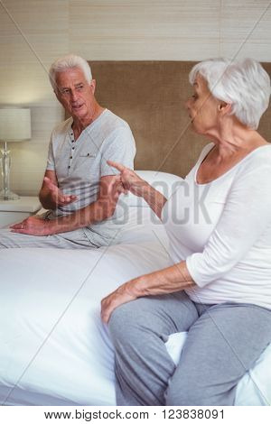 Senior couple quarreling while sitting on bed in room