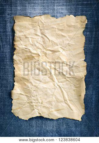 old crumpled paper lies on denim background