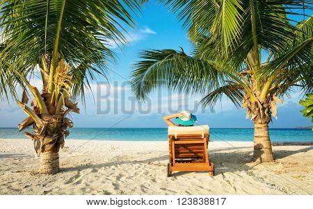 Woman relaxing on deckchair, tropical beach of Indian ocean, Maldives