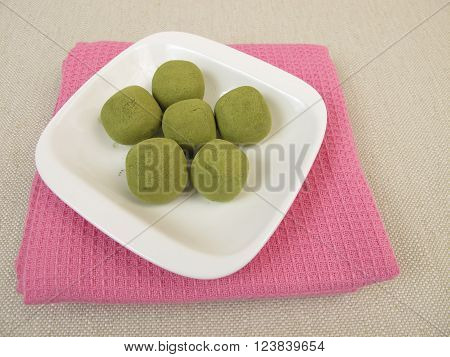 Green matcha praline balls in small bowls