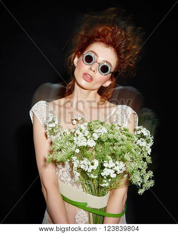 vogue fashion model woman with professional make up and hairstyle in sunglasses with flowers bouqet on dark background ** Note: Soft Focus at 100%, best at smaller sizes