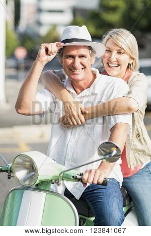 Portrait of smiling couple sitting motor scooter in city