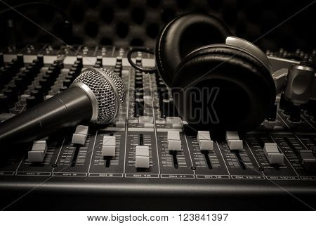 microphone and headphone on sound mixer background.