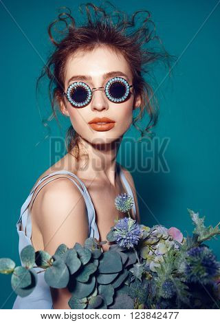 Beautiful fashion hipster in vogue sunglasses and flowers bouqet . model woman with professional make up and hairstyle on blue background . photo
