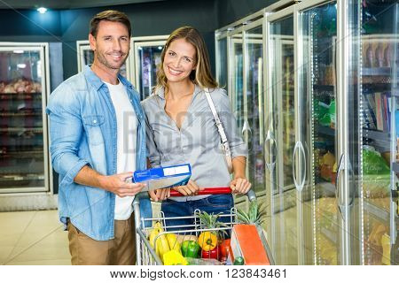 Happy couple buying frozen food at the grocery store