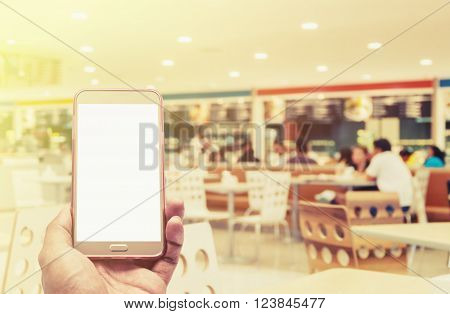 Hand with smartphone on blurred in food court background, Transaction by smartphone concept, Vintage style