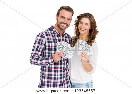 Portrait of happy young couple holding fanned out currency notes on white background