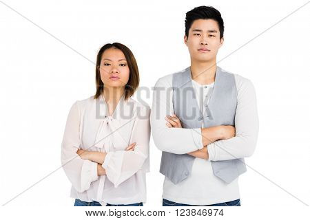 Upset couple standing with arms crossed on white background