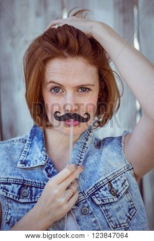 beautiful hipster woman holding a fake mustache to her face, against a wooden backhround