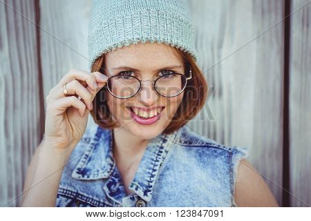 smiling hipster woman in a beanie and glasses against a wooden baackkground