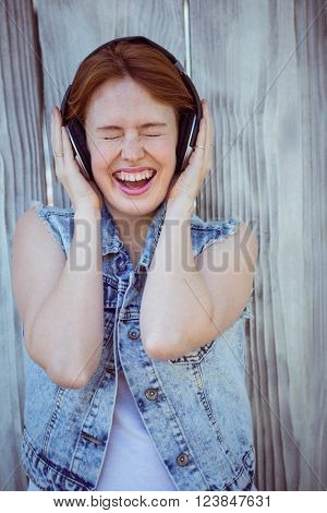 smiling hipster woman cupping her ears, listening to loud music