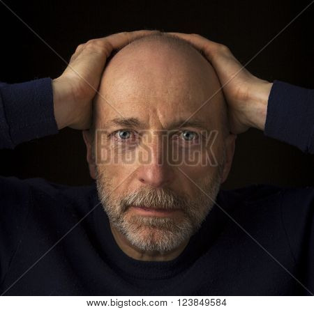 60 years old  bald man with a beard - a head shot against a black background