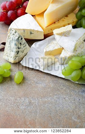 Different Types Of Cheese With Grapes On Slate