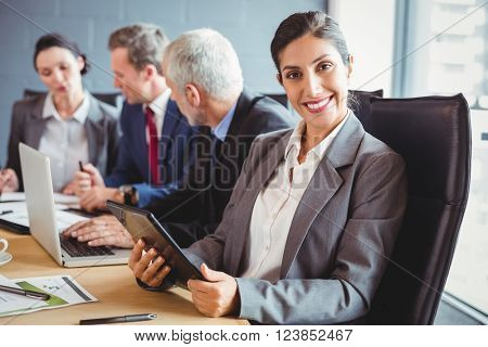 Businesswoman smiling at camera and businesspeople interacting in background in conference room during meeting