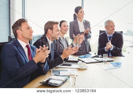 Businesspeople applauding in conference room during meeting