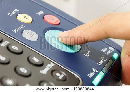 Finger's someone is pushing start copy machine .