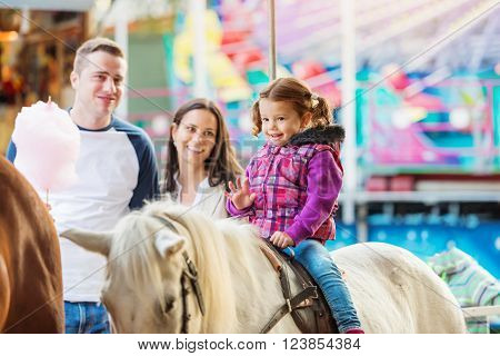 Little girl enjoying a ride on pony at fun fair, parents watching her, amusement park