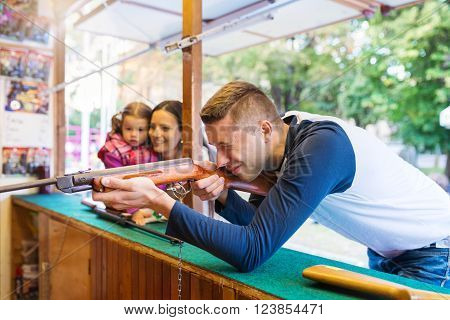 Young fun couple playing shooting games at amusement park