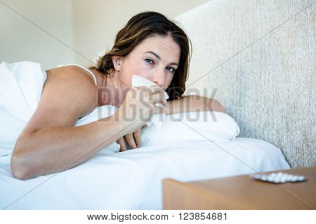 Sick woman lying in her bed wiping her nose