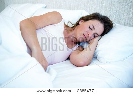 relaxed looking woman lying in her bed, asleep