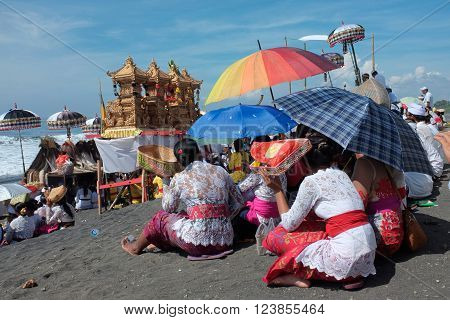 BALI INDONESIA - March 6 2016: Balinese Hindu pilgrims shade themselves from the sun and pray at the beach during an annual religious ceremony on March 6 2016 in Gianyar Bali Indonesia.
