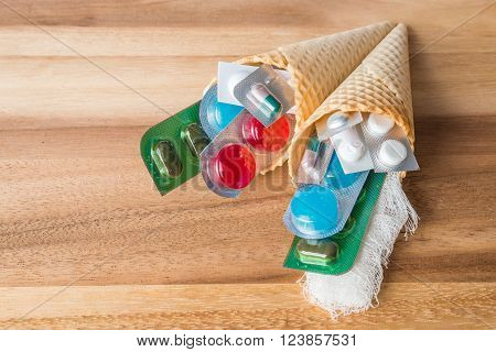 Mix of medicines and pills in wafer cones on wooden background