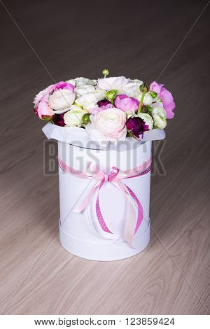 summer flowers in white round box on wooden table