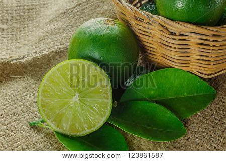 Still life selective focus to slice fresh lime and leaf lime on sack background.Many lime in the wood basket.